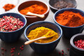 Spices in bowls: curry, pink and black pepper, paprika powder Stock Photography