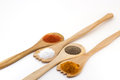 Spices on three wooden spoons isolated on white background