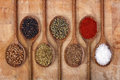 Spices on wooden spoons full of aromatic herbs and a wood cutting board Stock Photos