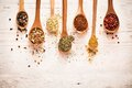 Spices in wooden spoons on white wooden background Royalty Free Stock Photography