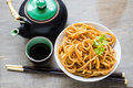 Spicy asian noodles a bowl of and a clay pot of tea Royalty Free Stock Photography