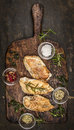 Spicy baked chicken breast on rustic wooden gutting board, top view Royalty Free Stock Photo