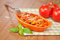 Spicy chicken penne pasta individual casserole dish with on checkered green cloth shallow depth of field Royalty Free Stock Photography