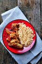 Spicy chicken wings with rice and herbs on an old wooden background
