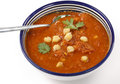 Spicy chickpea and tomato soup in a traditional tunisian bowl with a spoon garnished with parsley Stock Images