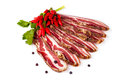 Spicy smoked bacon sliced slices of decorated with chili peppers on white background Stock Photos