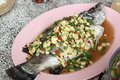 Spicy steamed sea bass with red chilli ingredient include garlic ginger and light soy sauce Royalty Free Stock Photo