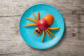 Spider made of juicy fruits on plate and desk Royalty Free Stock Photography
