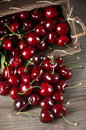 Spilled cherries from basket on wooden background Stock Image