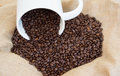 Spilled coffee beans from big mug Royalty Free Stock Photo