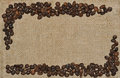 Spilled coffee beans frame over burlap textile Royalty Free Stock Photo