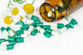 Spilled pills, a bottle and two flowers of chamomile Royalty Free Stock Photo