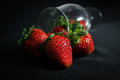 Spilled strawberries from a glass on black surface Royalty Free Stock Images