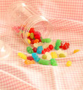 Spilt candy this photo shows in a jar and on to a pink gingham tablecloth Royalty Free Stock Images