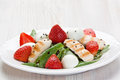 Spinach chicken strawberry salad grilled and quail eggs with balsamic vinegar on white plate Stock Photography