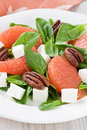 Spinach grapefruit goat cheese salad with pecan nut on white plate Royalty Free Stock Photography