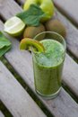 Spinach kiwi green apple smoothie in the glass leaves and lemon in the background Stock Photography