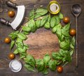 Spinach leaves have been laid out around a circular chopping board, with herbs and salad spoon, knife and salad, frame Royalty Free Stock Photo