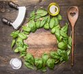 Spinach leaves have been laid out around a circular chopping board, with herbs and salad spoon, knife and salad,frame, space for Royalty Free Stock Photo