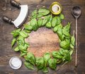 Spinach leaves have been laid out around a circular chopping board, with herbs and salad spoon, knife and salad, frame, space for Royalty Free Stock Photo