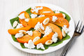 Spinach persimmon goat cheese salad with almond on white plate Stock Images