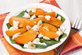 Spinach persimmon goat cheese salad with almond on white plate Stock Photos