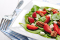 Spinach salad with strawberries goat s cheese and pecan nut Royalty Free Stock Photos