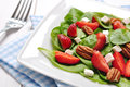 Spinach salad with strawberries goat s cheese and pecan nut Stock Photo
