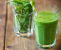 Spinach smoothie on wooden table Royalty Free Stock Image