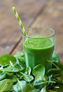 Spinach smoothie on wooden table Stock Images