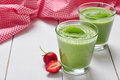 Spinach smoothies in glass served with strawberry on a wooden background Stock Photo