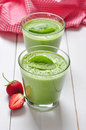 Spinach smoothies in glass served with strawberry on a wooden background Stock Photos