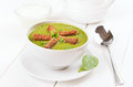 Spinach soup with dried crusts in white bowl Stock Image