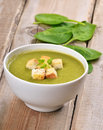 Spinach soup with dried crusts on wooden table Royalty Free Stock Images