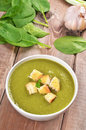 Spinach soup with dried crusts on wooden table Royalty Free Stock Photography