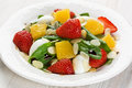Spinach strawberry orange salad and quail eggs with balsamic vinegar on white plate Royalty Free Stock Photo