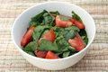 Spinach Tomato Salad with Salt and Coconut Oil in a White Bowl Stock Image