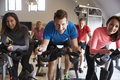 Spinning class on exercise bikes at a gym looking to camera Royalty Free Stock Photo