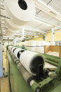 Spinning factory machinery rolls of fabric and in Stock Image