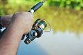 Spinning reel hand holding mounted on rod Stock Images