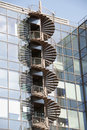 Spiral fire escape staircase on external wall of office block with reflections in curtain walling Royalty Free Stock Image