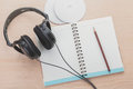 Spiral notebook and headphone on wood background