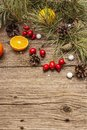 Spirit Christmas background. Fresh mandarins, dog-rose berries, candies, pine branches and cones, artificial snow Royalty Free Stock Photo