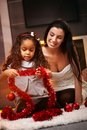 Spirit of christmas happy mother and ethnic daughter at time smiling playing with decorations Royalty Free Stock Image