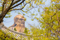 The spiritual creator of daoism laozi laoshan china a huge m statue seen through a forest above a chinese roof Stock Photo
