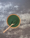 Spirulina algae powder overhead view of a wooden bowl and spoon filled with blank space Royalty Free Stock Image