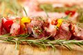 Spit of spiced raw pork meat with pepper on a wooden board closeup and red and yellow selective focus Royalty Free Stock Images