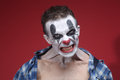 Spöklik clown portrait på röd bakgrund Arkivfoton