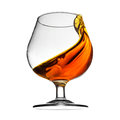 Splash of cognac in glass on white background see my other works portfolio Royalty Free Stock Images