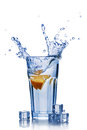 Splash in glass of blue water with orange slice and ice cube Royalty Free Stock Photo